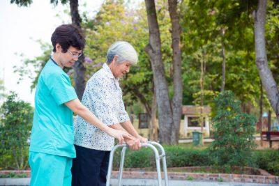 Nurse helps women with walker